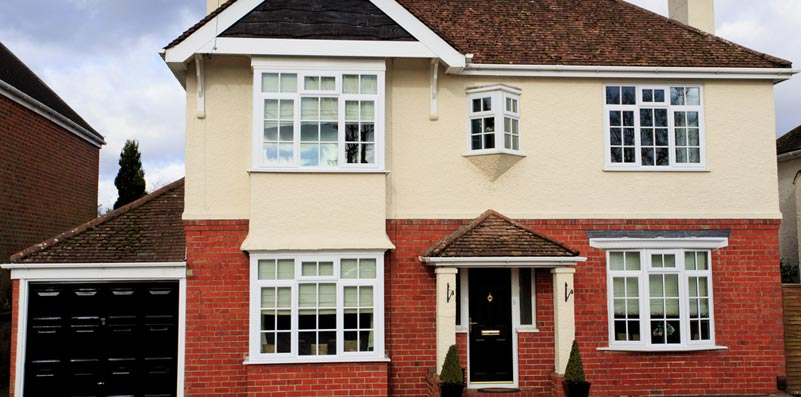 Full house with new white windows and black front door with archway